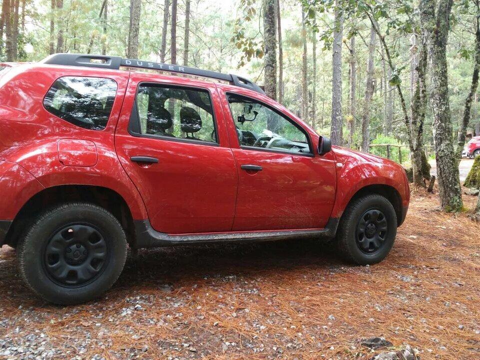Camioneta roja Duster renault en el bosque.